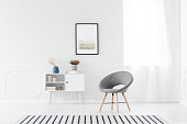 Grey chair and white cupboard against the wall with poster in simple living room interior with window