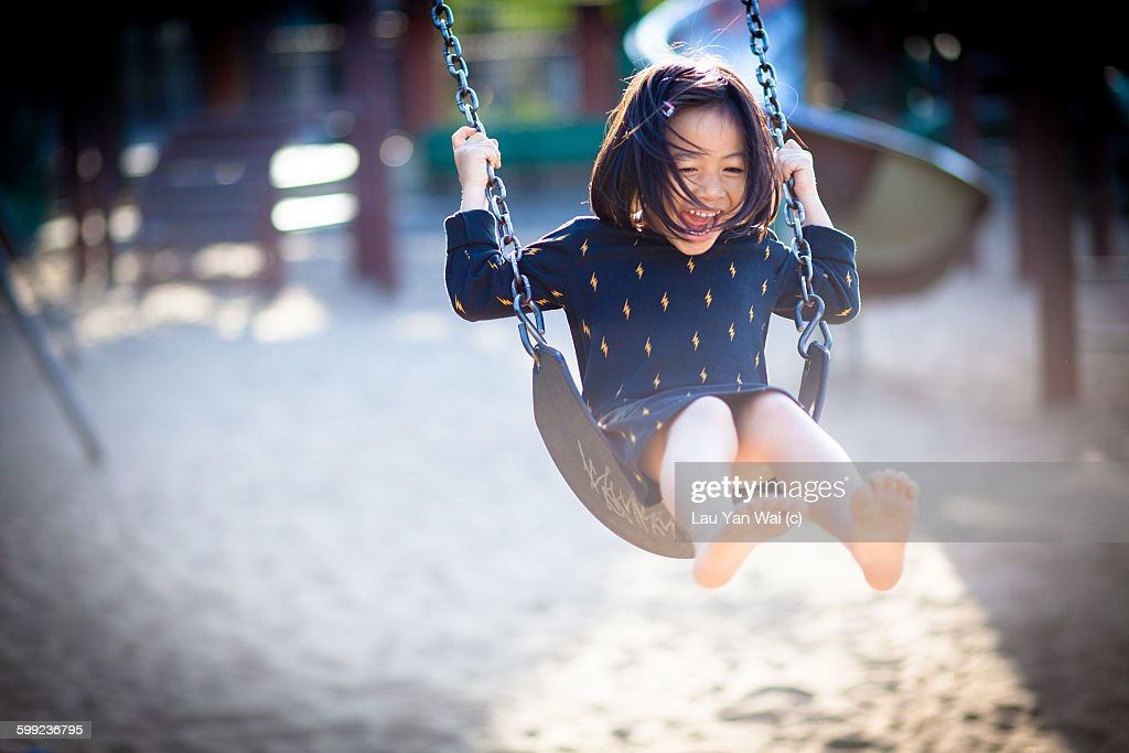 Girl swinging and laughing.