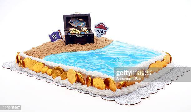 A simple sheet cake gets a pirate theme with a craftstore treasure chest a 'beach' of brown sugar and an 'ocean' of bluetinted decorating gel on a...