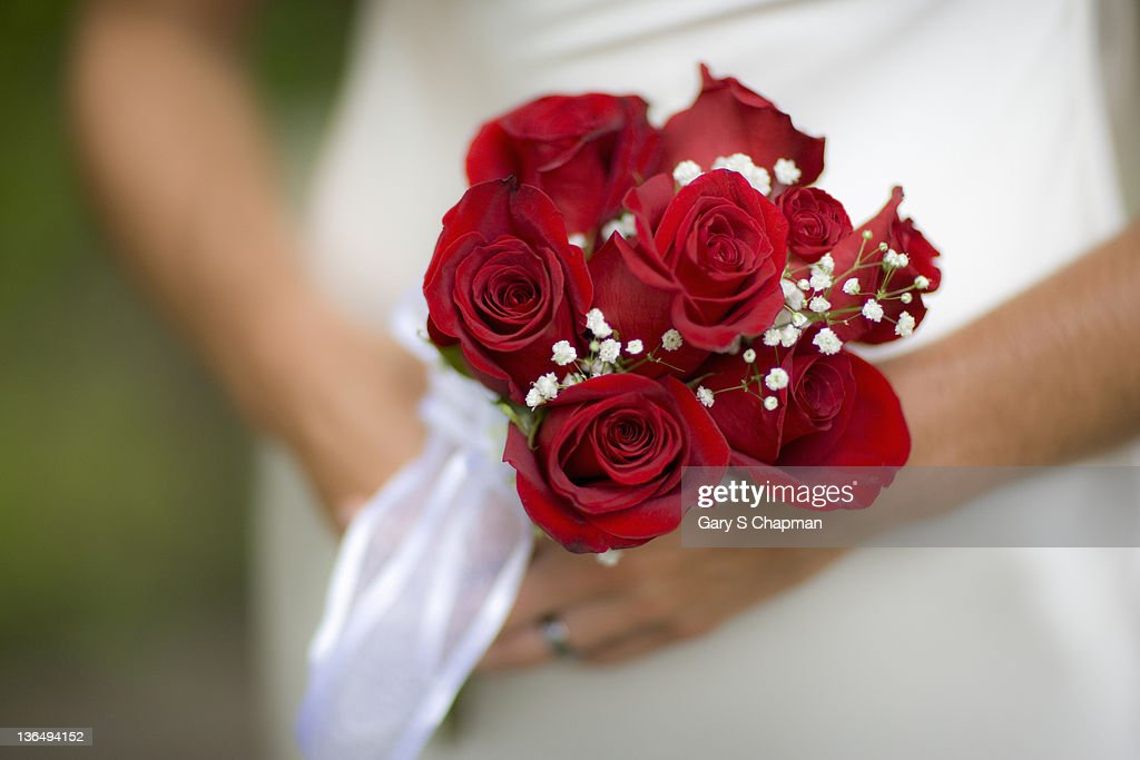 Simple wedding bouquet of roses held by bride : Stock Photo