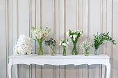 simply composition of different white flower in vase on white vintage table