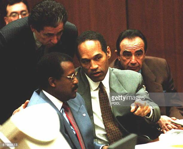 J Simpson confers with attorneys Johnnie Cochran and Robert Shapiro during 24 January hearing in Simpson's murder trial in Los Angeles CA Judge Lance...