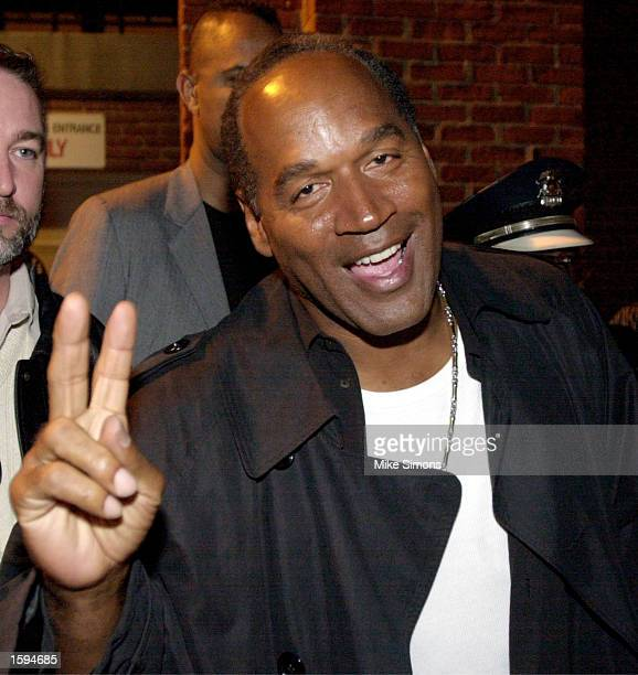 O J Simpson flashes a peace sign as he makes his way to his limo after MCing a rap concert March 2 2002 in CIncinnati Ohio A judge issued a bench...
