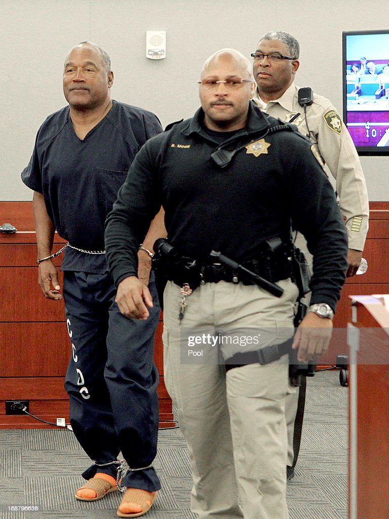 O.J. Simpson (L) is escorted by Ric Moon, Clark County Marshal and Las Vegas Police correctional officer George Gafford (R) during a break in an evidentiary hearing in Clark County District Court May 15, 2013 in Las Vegas, Nevada. Simpson, who is currently serving a nine to 33-year sentence in state prison as a result of his October 2008 conviction for armed robbery and kidnapping charges, is using a writ of habeas corpus to seek a new trial, claiming he had such bad representation that his conviction should be reversed.