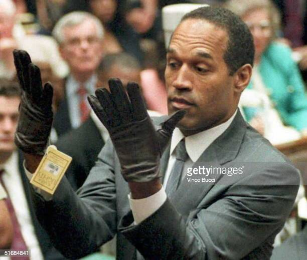 OJ Simpson looks at a new pair of Aris extralarge gloves that prosecutors had him put on 21 June 1995 during his doublemurder trial in Los Angeles...