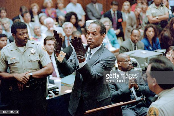 OJ Simpson looks at a new pair of Aris extralarge gloves which the prosecutors had him put on for the jury 21 June 1995 during his double murder...