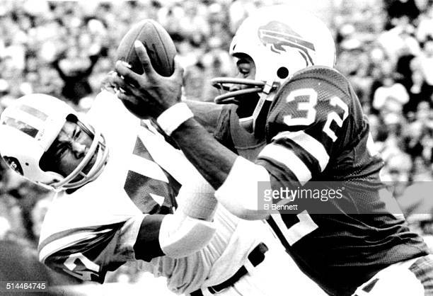 J Simpson of the Buffalo Bills runs with the ball as Roscoe Word of the New York Jets goes for the tackle on September 22 1975 at Rich Stadium in...