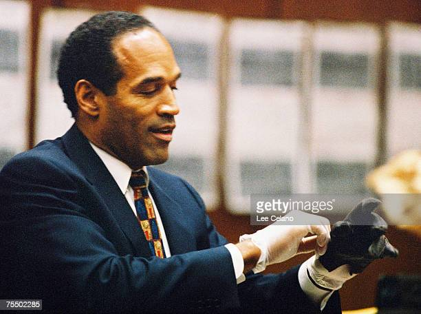 OJ Simpson tries on a leather glove allegedly used in the murders of Nicole Brown Simpson and Ronald Goldman during testimony in Simpson's murder...