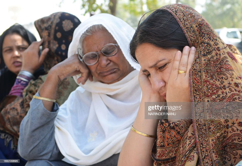 Simrjeet Kaur (R) the wife of late Indian Punjab Police assistant sub-inspector (ASI) Kulbir Singh and his mother Kailash Kaur (C) mourn after his death outside a hospital in Tarn Taran district about 25 kms(15 miles) from Amritsar on March 6, 2013. Singh died after allegedly being held hostage by farmers in Punjab's Tarn Taran district, who said he died of a heart attack. The farmers were protesting against recent fuel price hikes and were blocking railway traffic. Later, ruling out any foul play in the ASI's death, Tarn Taran senior superintendent of police (SSP) said he died of normal causes. AFP PHOTO/ NARINDER NANU