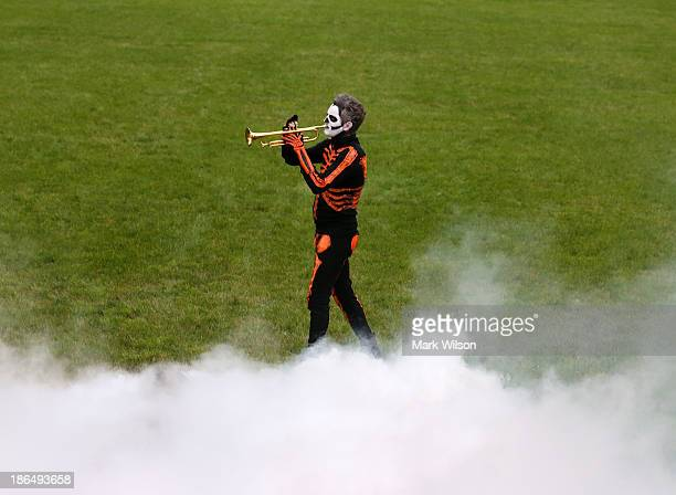 Simulated smoke fills the air as a musician in costume plays the Trumpet while US President Barack Obama first lady Michelle Obama give out treats to...