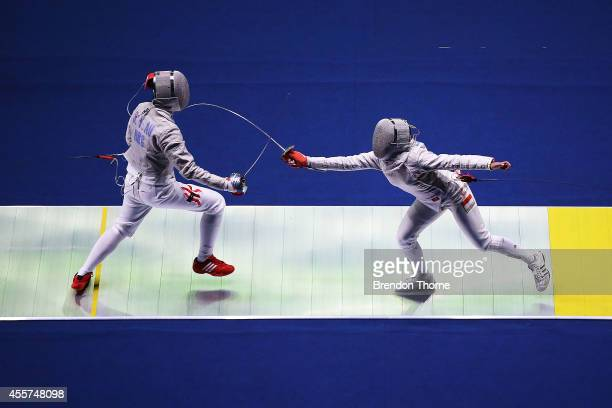 Sin Ying Au of Hong Kong and Diah Permatasari of Indonesia compete in the Women's Sabre Round of 16 during day one of the 2014 Asian Games at Goyang...