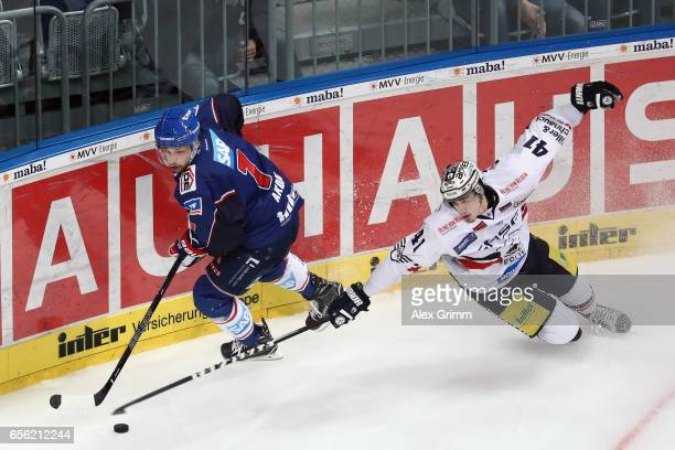 Sinan Akdag of Mannheim is challenged by LouisMarc Aubry of Berlin during the DEL Playoffs quarter finals Game 7 between Adler Mannheim and...