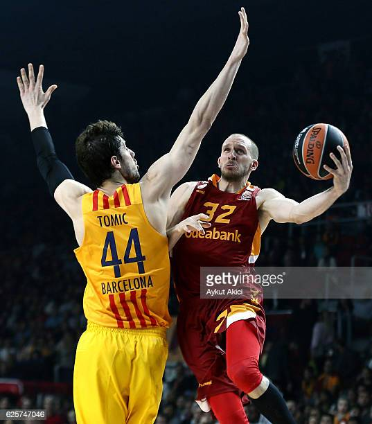 Sinan Guler #32 of Galatasaray Odeabank Istanbul competes with Ante Tomic #44 of FC Barcelona Lassa during the 2016/2017 Turkish Airlines EuroLeague...