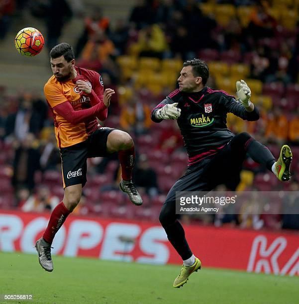 Sinan Gumus of Galatasaray is in action against Ernestas Setkus of Medicana Sivasspor during the Turkish Spor Toto Super Lig match between...