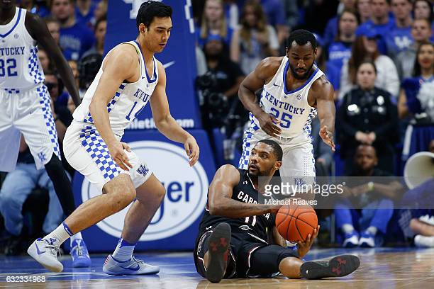 Sindarius Thornwell of the South Carolina Gamecocks looks to pass defended by Tai Wynyard and Dominique Hawkins of the Kentucky Wildcats during the...