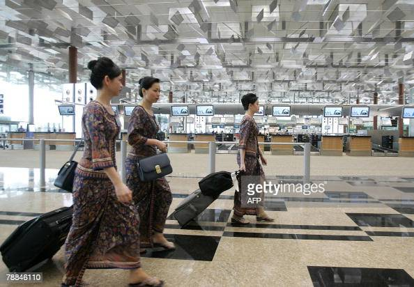 Singapore Airlines stewardesses walk through the departure hall of Changi International Airport Terminal in Singapore 09 January 2008 Singapore...