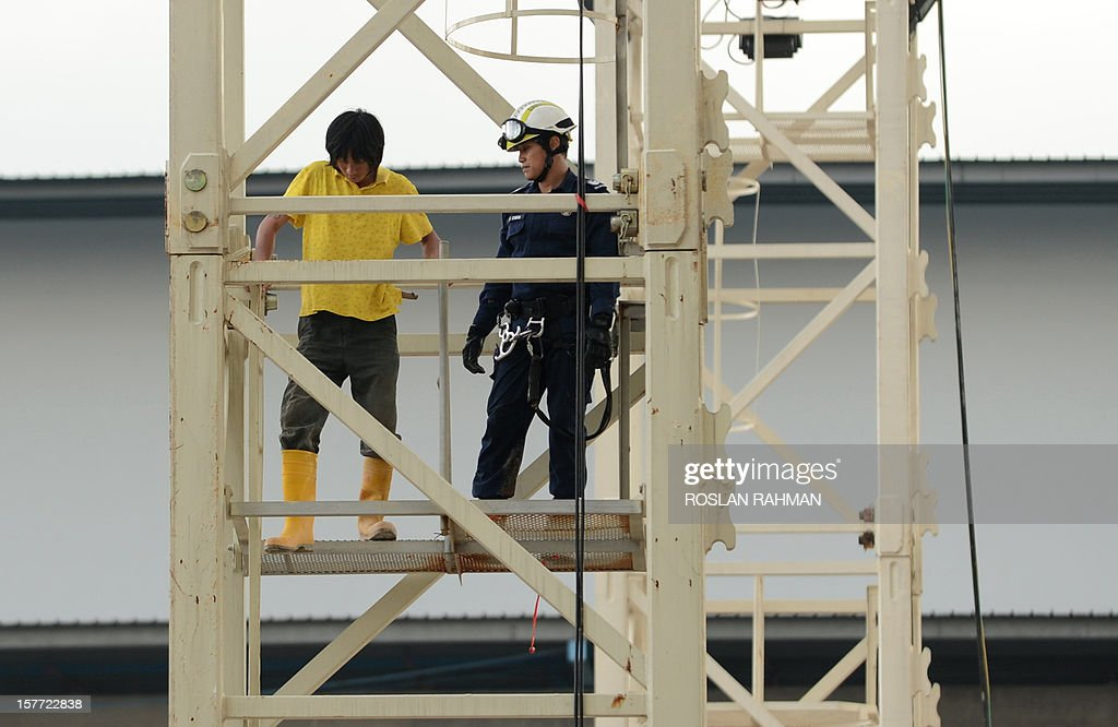 A Singapore civil defense force officer (R) assists a mainland Chinese worker down from a crane after protesting at a construction site in Singapore on December 6, 2012. Two crane operators staged a high-rise protest at a construction site in Singapore on December 6, its second industrial incident involving mainland Chinese workers in less than two weeks. AFP PHOTO / ROSLAN RAHMAN
