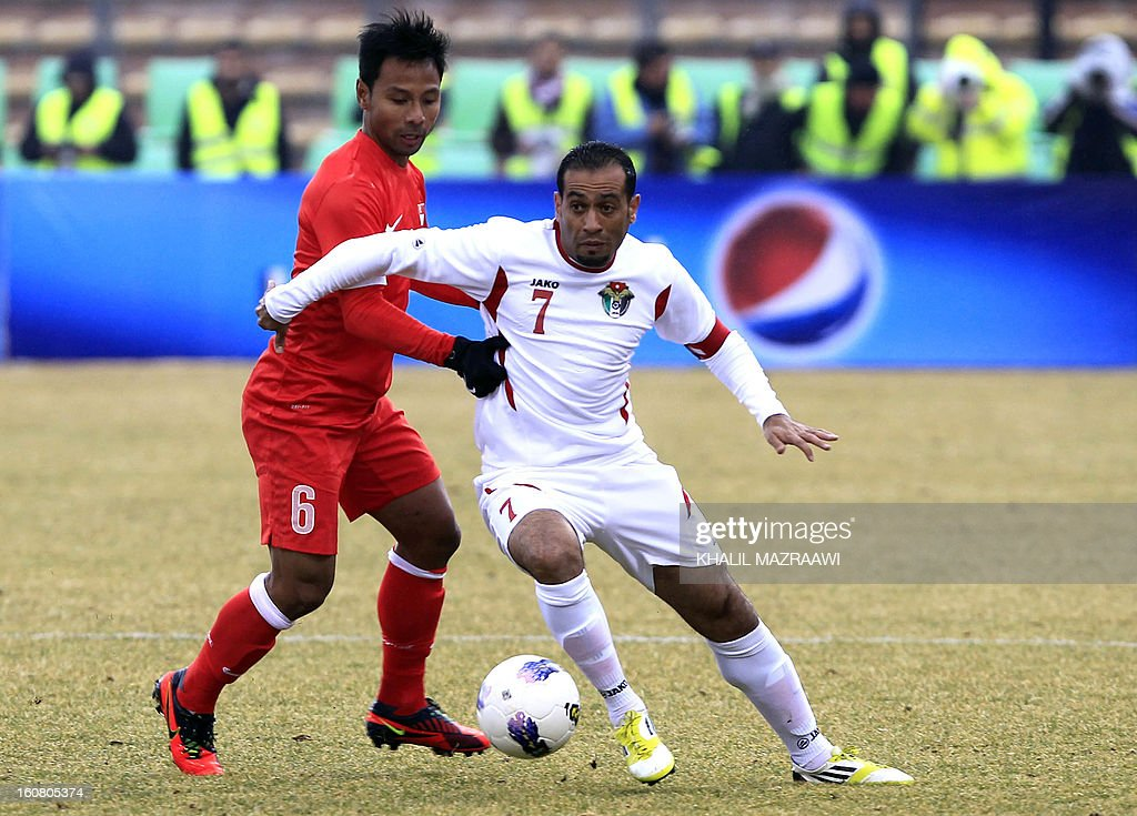 Singapore defender Noh Rahman (L) vies for the ball against Jordan's Amer Deeb during their 2015 AFC Asian Cup group A qualifying football match at the King Abdullah International Stadium in the capital Amman, on February 6, 2013. AFP PHOTO/KHALIL MAZRAAWI