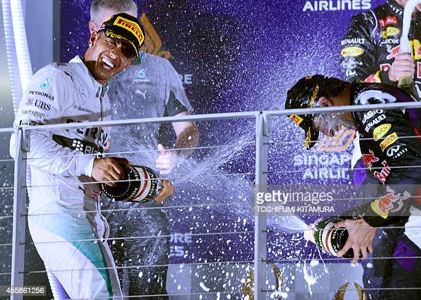 Singapore Formula One Grand Prix winner and Mercedes driver Lewis Hamilton of Britain sprays a bottle of champagne with third placed Red Bull Racing...