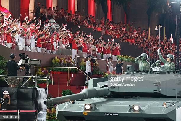 Singapore politicians wave as the mobile column display roll past the City Hall during the National Day Parade at Padang on August 9 2015 in...