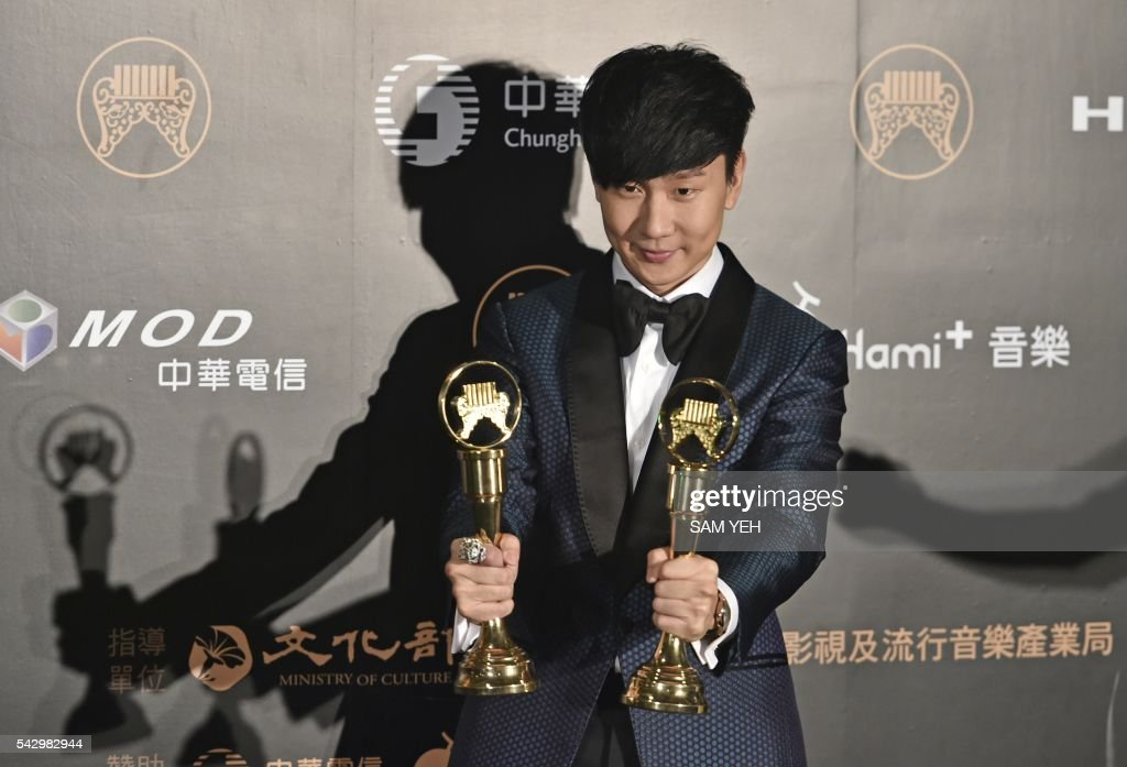 Singapore pop singer JJ Lam displays two trophies after winning the Best Composer and the Best Male Mandarin Singer awards during the 27th Golden Melody Awards in Taipei on June 25, 2016. Some of Mandarin pop's biggest names have gathered for the annual Golden Melody music awards, with singers, songwriters and composers from Taiwan, China, Hong Kong, Singapore and Malaysia competing in more than 20 categories. / AFP / SAM YEH