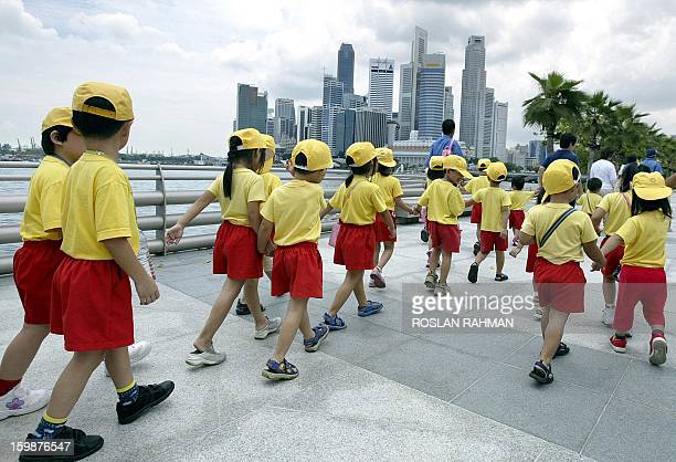 BABIES' Singapore preschool children walk along the bay during an excursion trip at the Singapore River waterfront 05 March 2004 A renewed effort is...