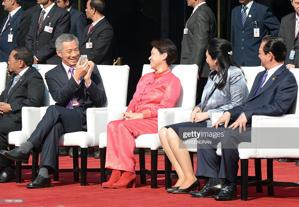 Singapore Prime Minister Lee Hsien Loong (L) takes a photograph his wife Ho Ching, as Prime Minister of Thailand Yingluck Shinawatra (2R) and Vietnam Prime Minister Nguyen Tan Dung look on during the ASEAN flag down ceremony in New Delhi on December 21, 2012. The leaders arrived in Delhi for the India-Association of Southeast Asian Nations (India-ASEAN) summit held from December 20-21. AFP PHOTO/ RAVEENDRAN