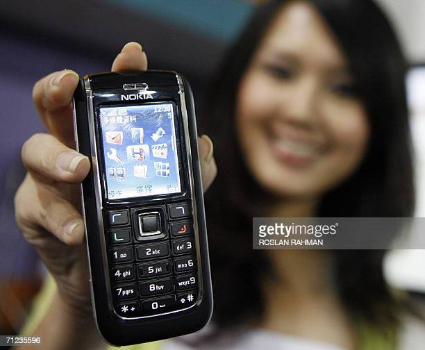 A model Julie Hoi displays the Nokia 6151 a thirdgeneration or 3G handset at the Nokia exhibition in Singapore 19 June 2006 Nokia the world's biggest...
