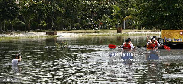 A photographer takes pictures of participants race on a raft in a waist level lake in Pulau Ubin off Singapore 03 February 2007The participants are...
