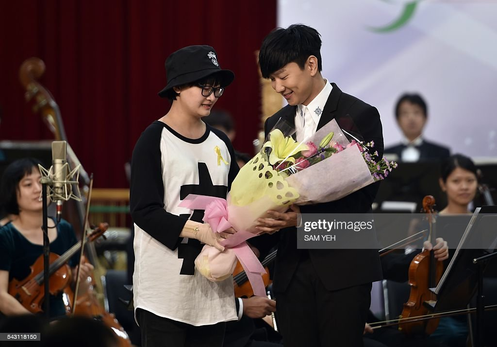 Singapore singer JJ Lin (R) receives flowers from a woman who was injured at an explosion at a water park last year, after performing during a music concert to mark the first anniversary of the accident in Taipei on June 26, 2016. Taiwan commemorated a water park explosion that left 15 dead and hundreds injured with a memorial concert on the eve of its one-year anniversary as victims and their relatives demanded justice after only a party organiser was sentenced over the incident. The accident happened in June 2015 at the Formosa Fun Coast water park near Taipei, when clouds of multi-coloured corn starch sprayed on revellers at a 'colour party' ignited after heat from stage lights triggered a blast that ripped through the crowd. / AFP / SAM YEH