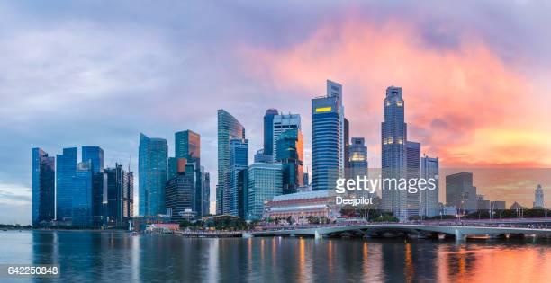 Skyline von Singapur an der Marina Bay in der Dämmerung mit glühenden Sonnenuntergang beleuchtet die Wolken