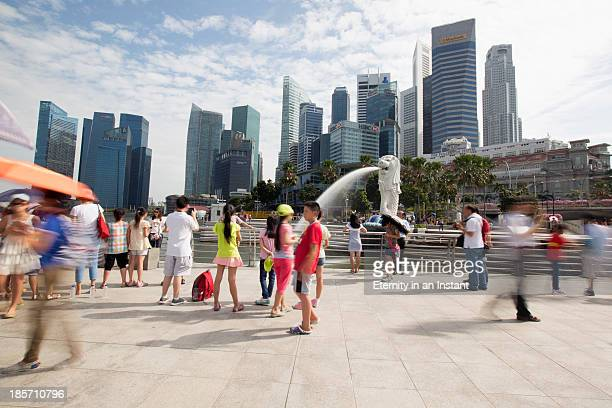 Singapore skyline with Merlion statue and tourists