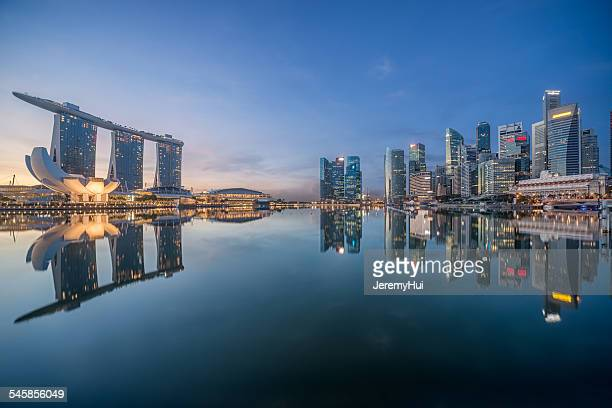 Singapore, Waterfront skyscrapers reflecting in still harbor in evening
