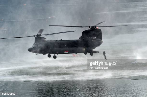 A Singaporean navy diver jumps out from a low flying Chinook helicopter during the 52nd National Day parade and celebration in Singapore on August 9...