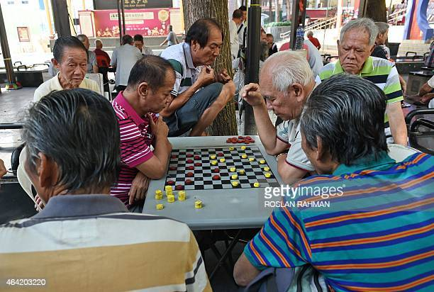 Singaporeans play checkers in the Chinatown district in Singapore on February 23 2015 Singapore's consumer prices fell 04 percent yearonyear in...