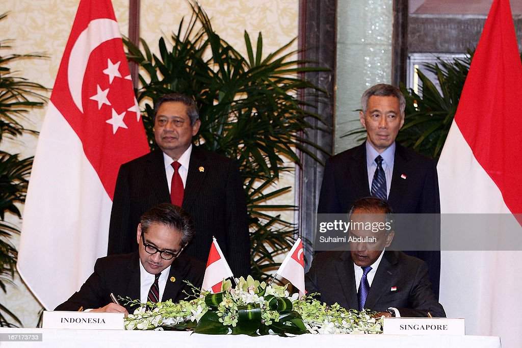 Singapore's Foreign Minister for Foreign Affairs, Mr K Shanmugam (front-R) and Indonesian Minister of Foreign Affairs, H.E. <a gi-track='captionPersonalityLinkClicked' href=/galleries/search?phrase=Marty+Natalegawa&family=editorial&specificpeople=2862416 ng-click='$event.stopPropagation()'>Marty Natalegawa</a> (front-L) sign a Memorandum of Understanding (MOU) on Cooperation on Diplomatic Education and Training at the Singapore-Indonesia Leaders' Retreat witnessed by Indonesian president, Dr <a gi-track='captionPersonalityLinkClicked' href=/galleries/search?phrase=Susilo+Bambang+Yudhoyono&family=editorial&specificpeople=206513 ng-click='$event.stopPropagation()'>Susilo Bambang Yudhoyono</a> (back-L) and Singapore's Prime Minister Mr <a gi-track='captionPersonalityLinkClicked' href=/galleries/search?phrase=Lee+Hsien+Loong&family=editorial&specificpeople=3911578 ng-click='$event.stopPropagation()'>Lee Hsien Loong</a> (back-R) on April 22, 2013 in Singapore. It is reported that President <a gi-track='captionPersonalityLinkClicked' href=/galleries/search?phrase=Susilo+Bambang+Yudhoyono&family=editorial&specificpeople=206513 ng-click='$event.stopPropagation()'>Susilo Bambang Yudhoyono</a> will hold a Leaders' Retreat with Singapore's Prime Minister <a gi-track='captionPersonalityLinkClicked' href=/galleries/search?phrase=Lee+Hsien+Loong&family=editorial&specificpeople=3911578 ng-click='$event.stopPropagation()'>Lee Hsien Loong</a> as part of the visit.