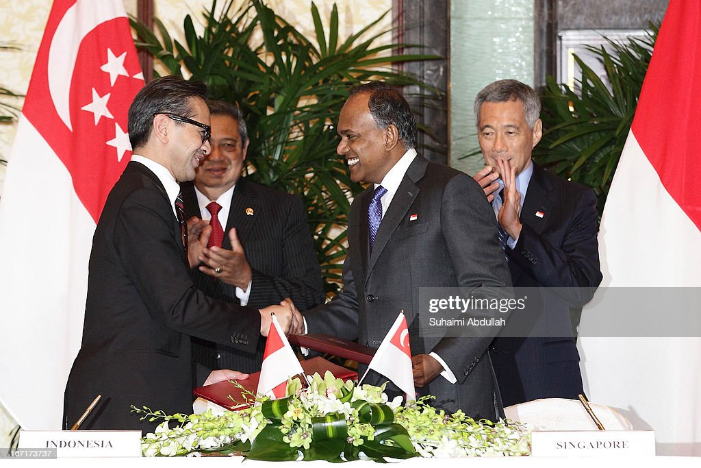 Singapore's Foreign Minister for Foreign Affairs, Mr K Shanmugam (front-R) shakes hands with Indonesian Minister of Foreign Affairs, H.E. <a gi-track='captionPersonalityLinkClicked' href=/galleries/search?phrase=Marty+Natalegawa&family=editorial&specificpeople=2862416 ng-click='$event.stopPropagation()'>Marty Natalegawa</a> (front-L) after signing the Memorandum of Understanding (MOU) on Cooperation on Diplomatic Education and Training at the Singapore-Indonesia Leaders' Retreat witnessed by Indonesian president, Dr <a gi-track='captionPersonalityLinkClicked' href=/galleries/search?phrase=Susilo+Bambang+Yudhoyono&family=editorial&specificpeople=206513 ng-click='$event.stopPropagation()'>Susilo Bambang Yudhoyono</a> (back-L) and Singapore's Prime Minister Mr <a gi-track='captionPersonalityLinkClicked' href=/galleries/search?phrase=Lee+Hsien+Loong&family=editorial&specificpeople=3911578 ng-click='$event.stopPropagation()'>Lee Hsien Loong</a> (back-R) on April 22, 2013 in Singapore. It is reported that President <a gi-track='captionPersonalityLinkClicked' href=/galleries/search?phrase=Susilo+Bambang+Yudhoyono&family=editorial&specificpeople=206513 ng-click='$event.stopPropagation()'>Susilo Bambang Yudhoyono</a> will hold a Leaders' Retreat with Singapore's Prime Minister <a gi-track='captionPersonalityLinkClicked' href=/galleries/search?phrase=Lee+Hsien+Loong&family=editorial&specificpeople=3911578 ng-click='$event.stopPropagation()'>Lee Hsien Loong</a> as part of the visit.
