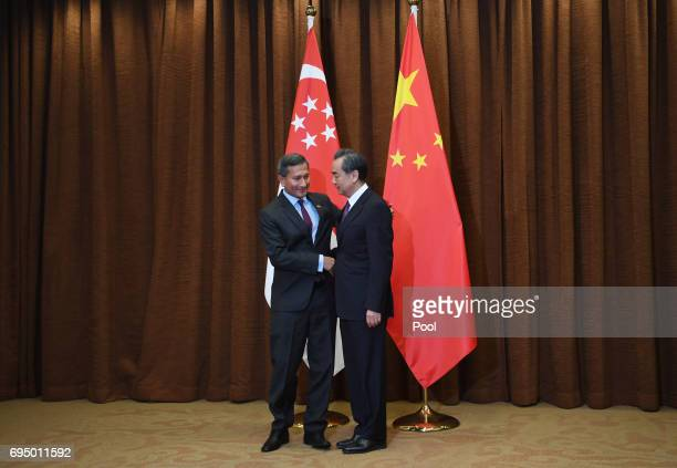 Singapore's Foreign Minister Vivian Balakrishnan shakes hands with Chinese Foreign Minister Wang Yi before a meeting at the Ministry of Foreign...