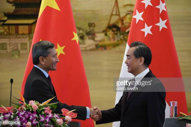 Singapore's Foreign Minister Vivian Balakrishnan shakes hands with Chinese Foreign Minister Wang Yi during a joint press conference at the Ministry...