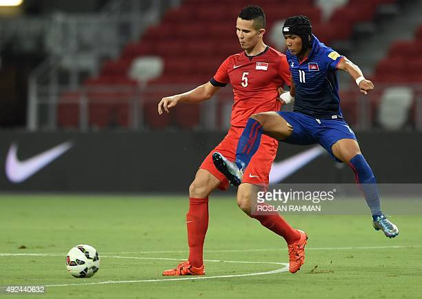 Singapore's forwarder Baikhaki Khaizan fights for the ball with Cambodia's midfielder Chan Vathanaka during their 2018 FIFA World Cup qualifier group...