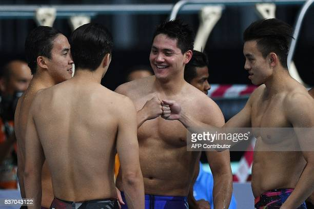 Singapore's Joseph Schooling celebrates with teammates after winning the men's swimming 4 X 100m freestyle relay final of the 29th Southeast Asian...