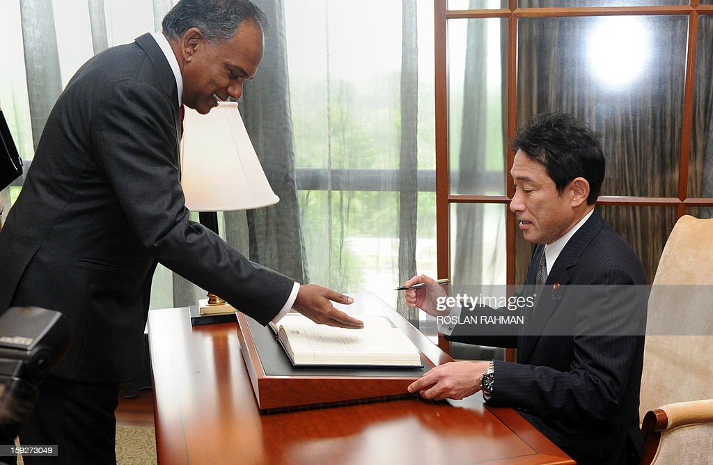 Singapore's Minister for Foreign Affairs and Minister for Law K. Shanmugam (L) shows the guest book to Japanese Foreign Minister Fumio Kishida (R) during his visit in Singapore on January 11, 2013. Kishida is on a two-day official visit as part of his Asia-Pacific tour.