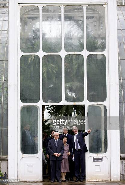 Singapore's President Tony Tan Keng Yam exits the the Palm House Tropical Rainforest with his wife Mary and Kew director Richard Deverell during...