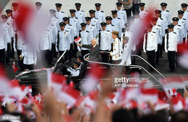 Singapore's President Tony Tan waves his country's flag during a drive past for the 52nd Singapore National Day parade and celebration in Singapore...