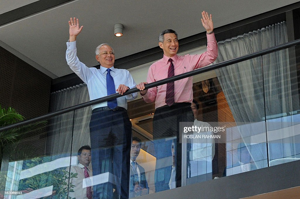 Singapore's Prime Minister Lee Hsien Loong (R) and Malaysia's Prime Minister Najib Razak (L) wave from the balcony of a showroom during the Marina One unveiling ceremony in Singapore on February 19, 2013. Singapore and Malaysia announced plans February 19 to build a high-speed rail link, fuelling hopes that Southeast Asia could one day enjoy a rapid European-style train system connected to China.