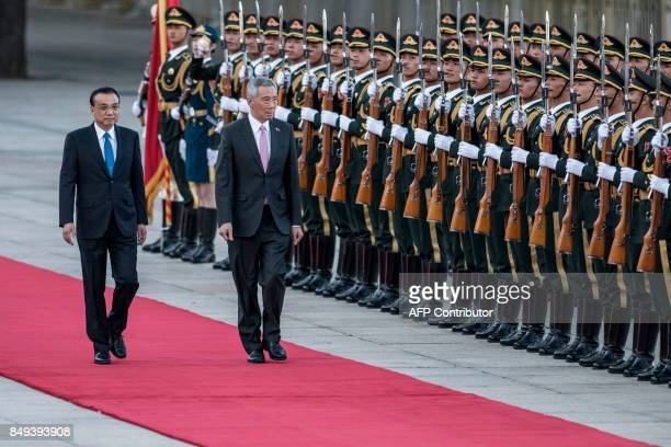 Singapore's Prime Minister Lee Hsien Loong inspects a guard of honour with Chinese Premier Li Keqiang during a welcome ceremony at the Great Hall of...