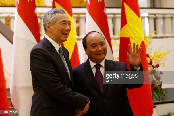 Singapore's Prime Minister Lee Hsien Loong is welcome by Vietnam's Prime Minister Nguyen Xuan Phuc in Hanoi on March 23 2017 Lee is on a fourday...