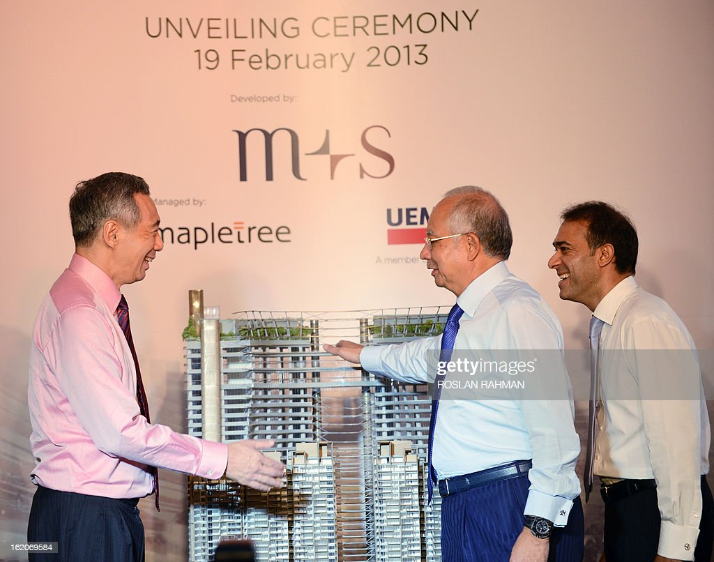 Singapore's Prime Minister Lee Hsien Loong (L), Malaysia's Prime Minister Najib Razak (C) and Azman Yahya (R), M+S board of directors chairman look at the building model display at the Marina One unveiling ceremony in Singapore on February 19, 2013. Singapore and Malaysia announced plans February 19 to build a high-speed rail link, fuelling hopes that Southeast Asia could one day enjoy a rapid European-style train system connected to China. AFP PHOTO / ROSLAN RAHMAN