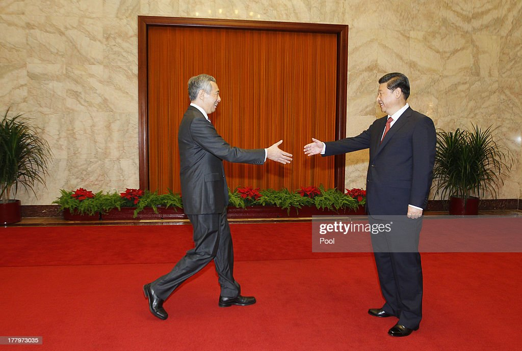 Singapore's Prime Minister Lee Hsien Loong (L) reaches to shake hands with Chinese President Xi Jinping at their meeting at the Great Hall of the People on August 26, 2013 in Beijing, China. Lee is on a seven-day visit to China where he will also visit China's Xinjiang Uygur Autonomous Region and Liaoning Province.