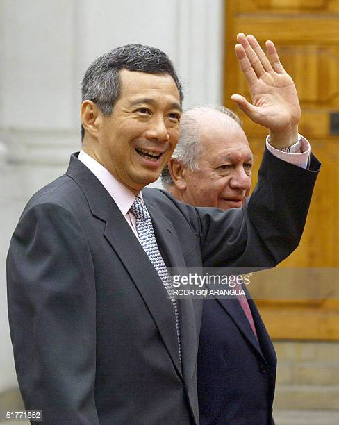 Singapore's Prime Minister Lee Hsien Loong waves next to Chilean President Ricardo Lagos as he enters at La Moneda Presidential Palace to attend the...